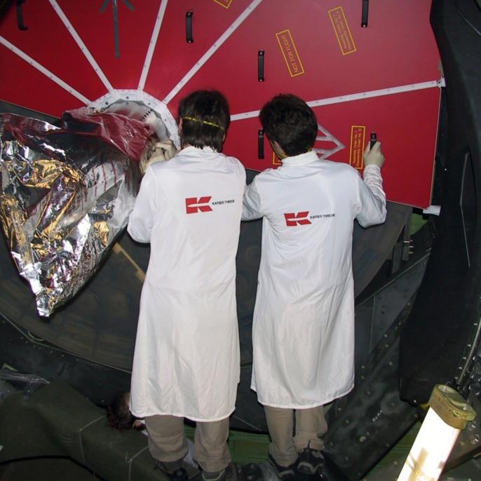 Zwei Ingenieure der Firma Kayser-Threde entfernen im Flugzeug den Schutz des SOFIA Primärspiegels, um das Teleskop für die erste Sternenbeobachtung bereit zu machen.